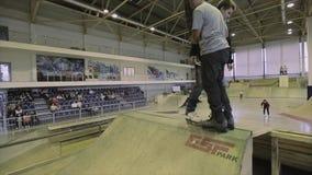 De tik van de rolschaatser in lucht ontbreek Twee schaatsers op springplank extreem Concurrentie in skatepark stock videobeelden
