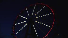 De timelapse étrange de nuit avec miroiter des lumières de roue de ferris tournant à l'arrière-plan des cieux nocturnes clips vidéos