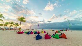 De Timelspaemensen liggen op een wit strand op hoofdkussens en ontmoeten de zonsondergang op het eiland Nusa Lembongan, Bali, Ind stock footage