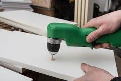 De timmerman boort een gat in de onderdelen van een witte kitche Stock Afbeelding
