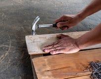 De Timmerman die houten raad nagelen om meubilair te maken stock foto's