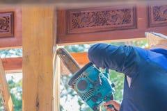 De timmerman gebruikt hout van de de kettingzaagbesnoeiing van de benzinemotor het draagbare aan verticale groeflijn Handen van d royalty-vrije stock fotografie