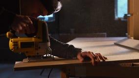 De timmerman houdt elektrische snijders voor het werk aangaande hout in een kleine onderneming stock videobeelden
