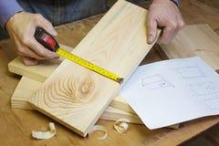 De timmerman maakt een vogelhuis in de workshop door schets stock afbeelding