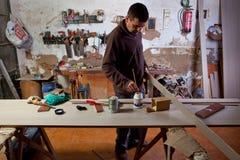 De timmerman past lijm op houten stuk toe Royalty-vrije Stock Afbeeldingen