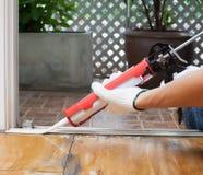 De timmerman past silicone toe waterdicht maakt op de houten vloer voor het verzegelen stock fotografie