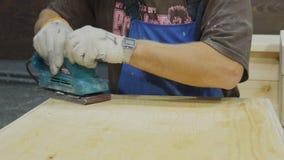 De timmerman poetst houten oppervlakte van het houten tafelblad met malende machine in zijn studio op stock footage