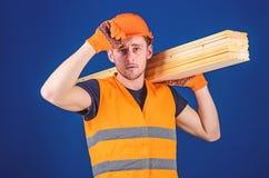 De timmerman, schrijnwerker, arbeider, bouwer draagt houten straal op schouder Schrijnwerkerconcept Mens in beschermende handscho stock afbeeldingen