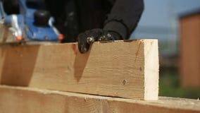 De timmerman sneed hout voor huisbouw stock video