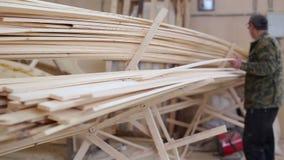 De timmerman verplaatst het hout in de stapel stock videobeelden