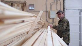 De timmerman verplaatst het hout in de stapel stock footage