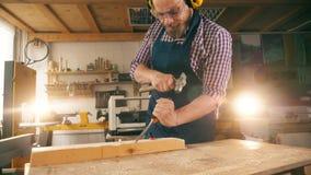 De timmerman verwerkt hout met een beitel en een hamer in langzame motie stock video