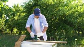 De timmerman zet op beschermende glazen en zand houten plank met elektrisch gereedschap stock video