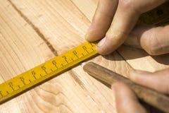 De timmermans` s handen wijzen op de afmeting op de raad met een potlood en een hoek stock afbeeldingen