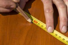 De timmermans` s handen wijzen op de afmeting op de raad met een potlood en een hoek royalty-vrije stock foto's