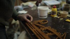 De timmermans` s workshop maakt met een schroevedraaier vast en boort de hangers aan de houder van medailles stock video