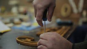 De timmermans` s workshop maakt met een schroevedraaier vast en boort de hangers aan de houder van medailles stock videobeelden