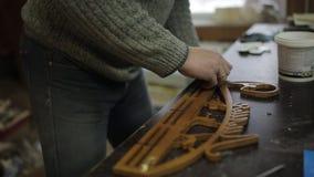 De timmermans` s workshop maakt met een schroevedraaier vast en boort de hangers aan de houder van medailles stock footage