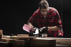De timmermanswerken met elektroplaner stock afbeelding