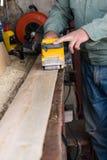 De timmermanswerken met riemschuurmachine in timmerwerk Stock Foto's