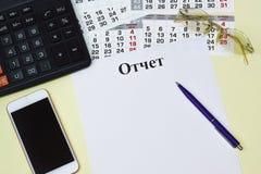 De titel in het Russische taalrapport over een blanco pagina, calculator, smartphone, zonnebril en een kalender stock fotografie