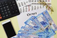 De titel in het Russische taalrapport over een blanco pagina, calculator, smartphone, zonnebril en nieuwe Russische bankbiljetten royalty-vrije stock foto's
