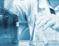 De titratie van de wetenschapperhand met buret en Erlenmeyer-fles, het onderzoek van het wetenschapslaboratorium en ontwikkelings stock foto