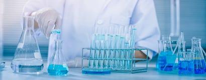 De titratie van de wetenschapperhand met buret en Erlenmeyer-fles, het onderzoek van het wetenschapslaboratorium en ontwikkelings Stock Afbeelding