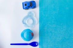 De toebehoren van de babyjongen en blauw speelgoed op witte achtergrond met lege ruimte voor tekst; hoogste mening, royalty-vrije stock afbeelding