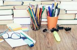 De toebehoren van de schoolkantoorbehoeften - notitieboekje, voorbeeldenboekstapel met plastic houderspotloden, pennen, tellers,  stock afbeeldingen