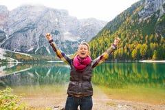 De toejuichingen van een gelukkige, het glimlachen vrouwenwandelaar voor vreugde bij Meer Bries Royalty-vrije Stock Afbeeldingen