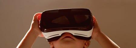 De toekomst is nu De kleine draadloze VR glazen van de kindslijtage Weinig kind in VR-hoofdtelefoon De aanbiddelijke moderne tech royalty-vrije stock afbeeldingen