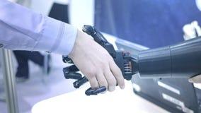 De toekomst is nu De mannelijke hand van de jonge uitvinder van de studentenwetenschapper schudt robotachtig wapen Hand van mens  stock videobeelden