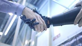 De toekomst is nu De mannelijke hand van de jonge uitvinder van de studentenwetenschapper schudt robotachtig wapen Hand van mens  stock video
