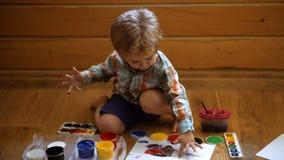 De toekomstige jongen van kunstenaarsTalented trekt een gele verf in kinderen` s centrum in hoofdklasse van art. stock videobeelden