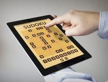 De toepassing van het Sudokuspel op een tablet Stock Foto's
