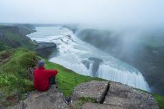 De toerist bekijkt de grote waterval in IJsland Royalty-vrije Stock Afbeeldingen