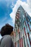 De toerist bekijkt moderne wolkenkrabber tegen blauwe hemel royalty-vrije stock afbeelding