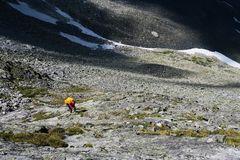 De toerist beklimt op de stenen in de bergen Het uitgaan van de rotsachtige morene royalty-vrije stock fotografie