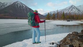 De toerist bevindt zich dichtbij het meer in mountais in de winter stock videobeelden