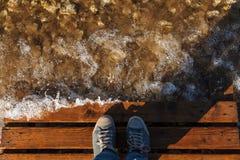 De toerist bevindt zich op een Houten brug De transparante golven van de rivier en de rotsachtige bodem Schoenen, hoogste mening royalty-vrije stock afbeelding