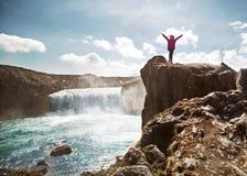 De toerist bevindt zich op een klip dichtbij een waterval, het concept van stock fotografie