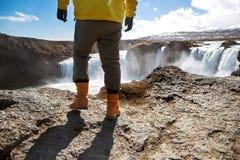 De toerist bevindt zich op een klip dichtbij een waterval, het concept van stock foto
