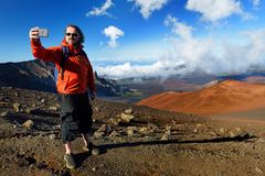 De toerist die een foto van zich in Haleakala-vulkaankrater nemen op het Glijdende Zand sleept Zij worden altijd gevuld met de vo stock afbeeldingen