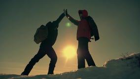 De toerist die teammate helpen beklimmen, de man met de rugzak bereikte uit een helpende hand aan zijn vriend Het schaak stelt bi stock videobeelden