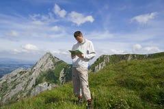 De toerist die van de berg kaart over blauwe hemel onderzoekt Stock Foto's