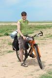 De toerist die van de fiets zich bij weg en het glimlachen bevindt Royalty-vrije Stock Foto