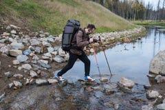 De toerist gaat rijke stroom over gebruikend trekkingspolen Stock Foto's