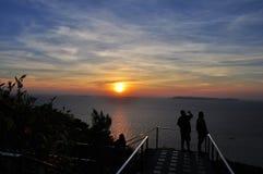 De toerist geniet van zonsondergang over het overzees stock foto