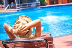 De toerist in hoed ligt op louger dichtbij zwembad voor ontspant het concept van de de zomervakantie stock afbeeldingen